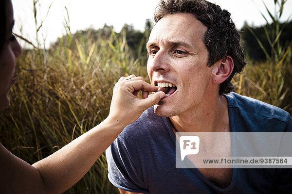 Frau Mann Picknick Olive füttern Seeufer