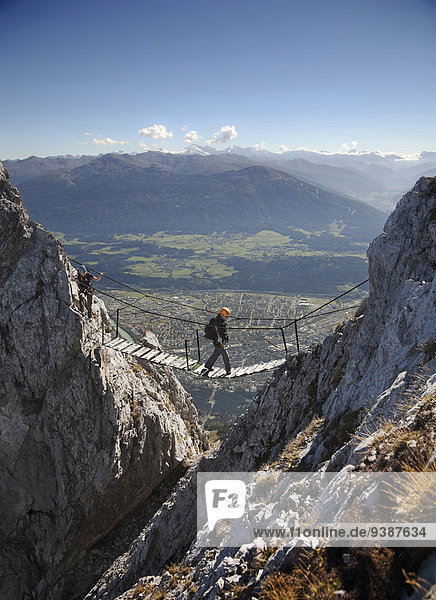 Female alpinists rock climbing  crossing a bridge  Innsbruck route  Tyrol  Austria
