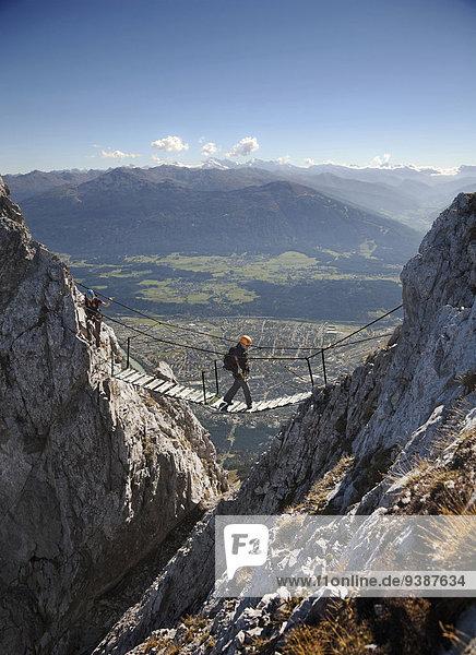 Female alpinists rock climbing,  crossing a bridge,  Innsbruck route,  Tyrol,  Austria