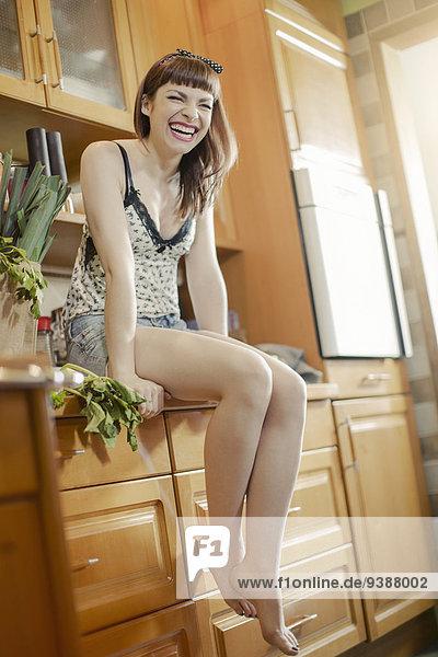 junge Frau junge Frauen sitzend lachen Küche