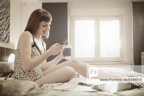junge Frau junge Frauen benutzen Tasse Bett trinken Kaffee Smartphone