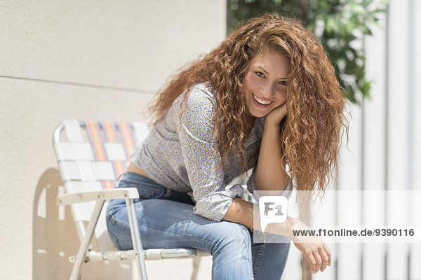 Portrait of woman sitting in deck chair outdoors