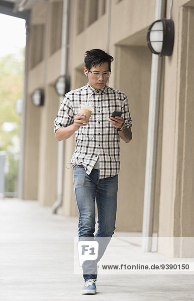 Man walking on sidewalk with iced coffee and mobile phone