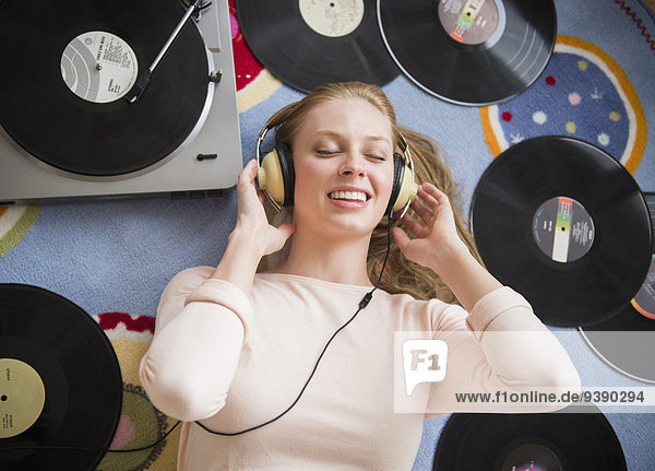 Young woman listening to music on vinyl record