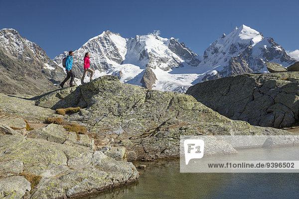Europa Frau Berg Mann gehen Eis wandern Ansicht Kanton Graubünden Moräne Engadin Schweiz