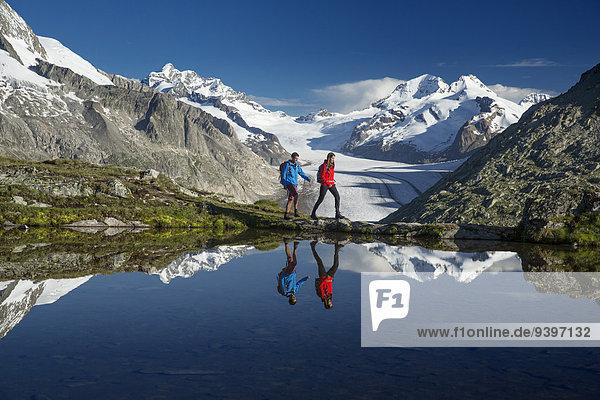 Freizeit Frau Berg Mann gehen Abenteuer Weg Spiegelung See Eis wandern Moräne Wanderweg Bergsee Aletschgletscher