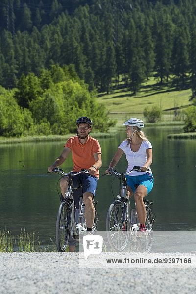 Frau Mann Sommer Fahrrad Rad Dorf Kanton Graubünden Fahrrad fahren Elektrofahrrad Ebike