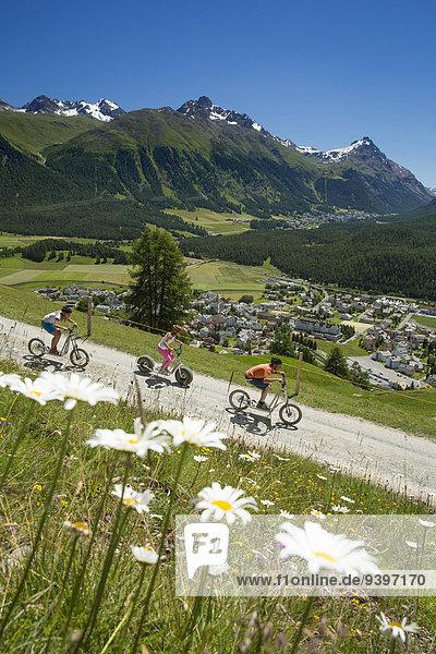 Frau Mann Sommer Fahrrad Rad Dorf gehen Kickboard Kanton Graubünden Roller Fahrrad fahren