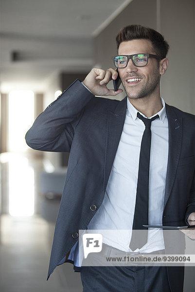 Geschäftsmann im Gespräch am Handy  digitales Tablett in der Hand