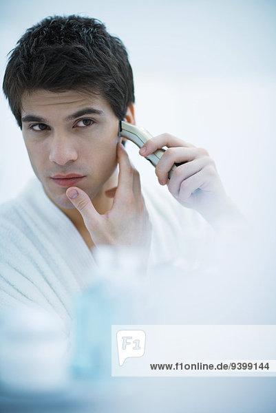 Junger Mann schaut in den Spiegel und rasiert sich mit einem elektrischen Rasierapparat.