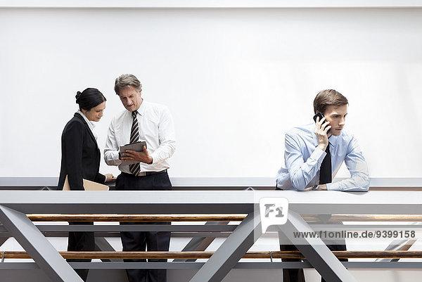 Geschäftsmann im Gespräch am Handy  Kollegen mit digitalem Tablett in der Nähe
