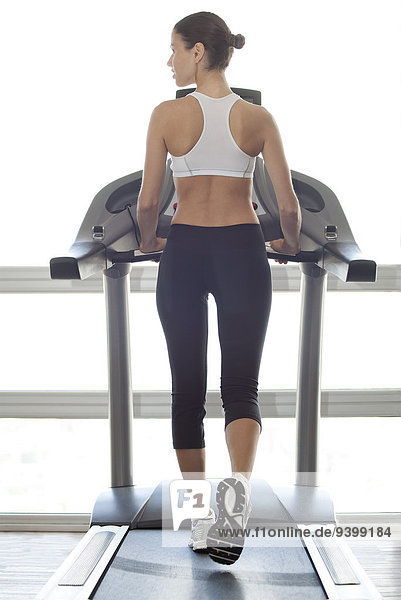 Frau trainiert auf dem Laufband