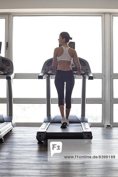 Frau joggen auf dem Laufband im Fitnessstudio