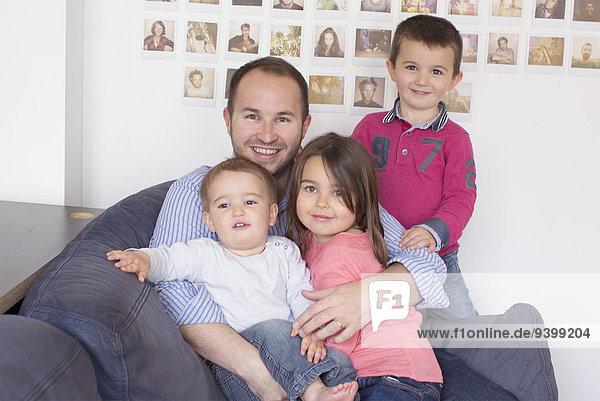 Vater und Kinder sitzen zusammen auf dem Sofa  Porträt