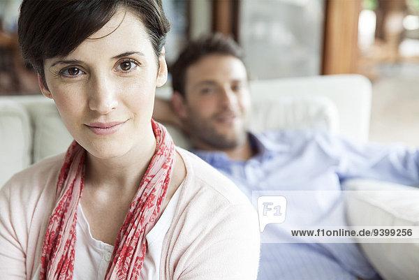 Frau im Wohnzimmer sitzend mit Mann im Hintergrund  Portrait
