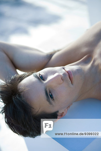 Nackter Mann auf dem Rücken liegend mit einer Hand hinter dem Kopf  Portrait