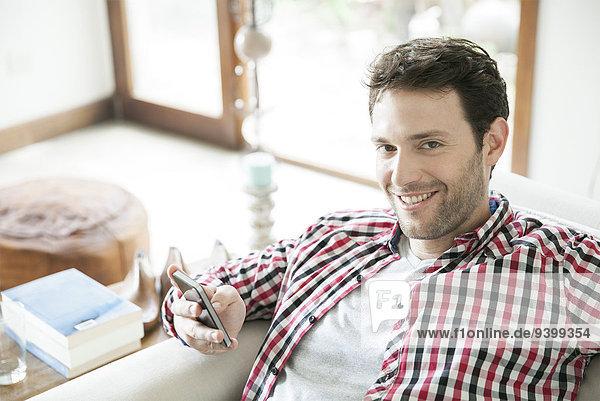 Mann mit Smartphone zu Hause  lächelnd