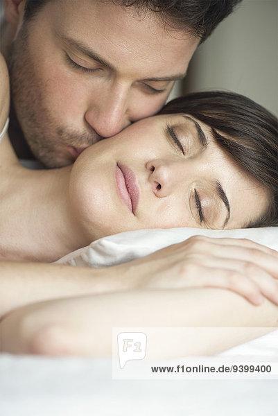 Ein Paar im Bett  der Mann küsst die Wange seiner Frau.