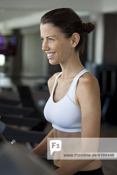 Frau beim Training auf dem Laufband im Fitnessstudio