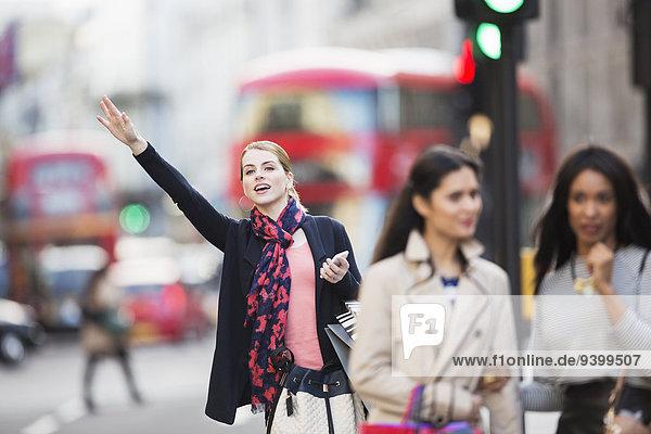 Frau signalisiert Taxi auf der Stadtstraße
