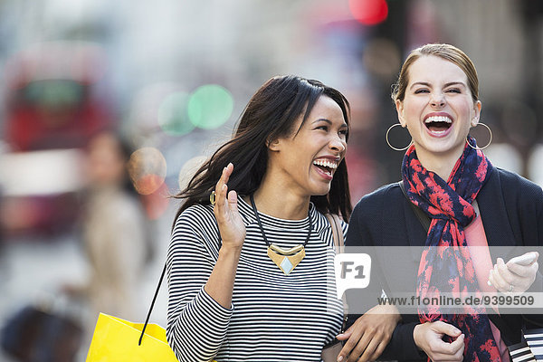 Frauen, die zusammen lachen, gehen die Straße entlang.