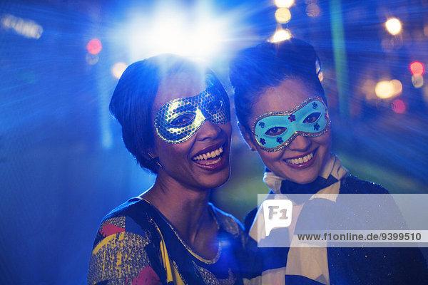Frauen in Masken lächeln zusammen