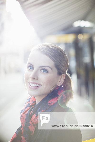 Frau lächelt an einem sonnigen Tag auf der Stadtstraße