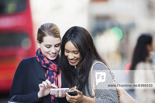 Frauen  die Mobiltelefone in der Stadt benutzen