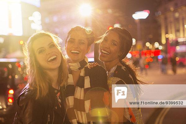 Frauen lachen gemeinsam auf der Stadtstraße