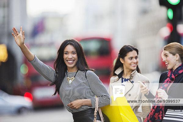 Frau ruft Taxi mit Freunden auf der Stadtstraße.