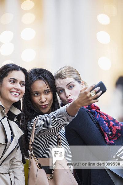 Frauen machen gemeinsam Handyfotos