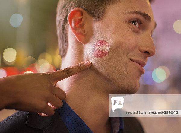 Mann posiert mit Lippenstiftdruck auf der Wange in der Stadt