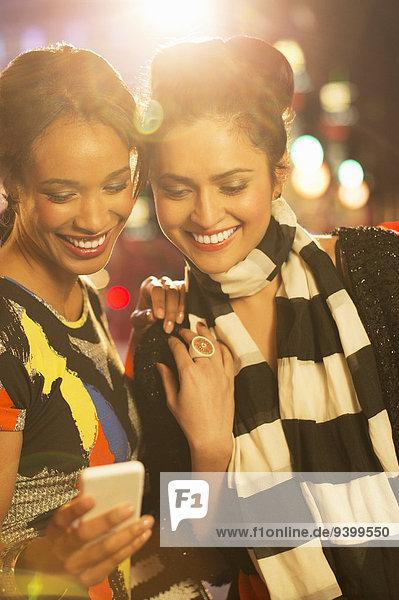 Frauen  die nachts gemeinsam auf dem Handy in der Stadt telefonieren.