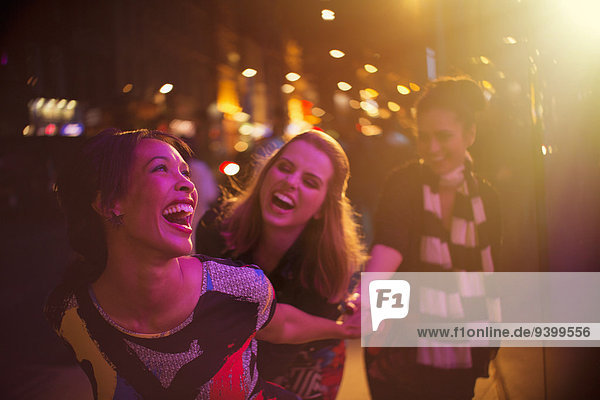 Women laughing together on city street at night