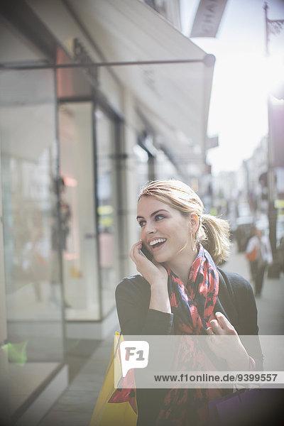 Frau, die auf dem Handy spricht, während sie die Straße entlang geht.