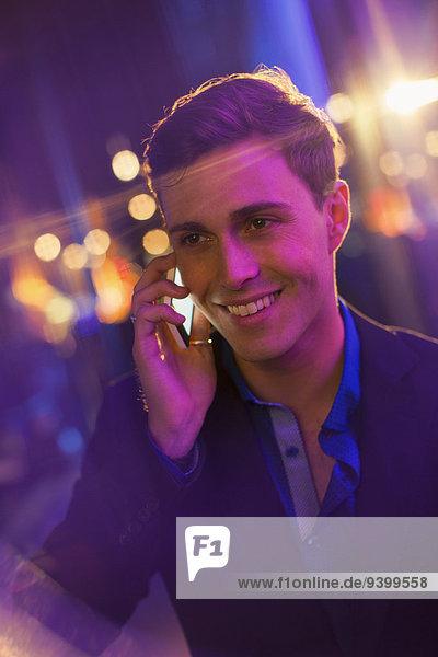 Ein Mann  der nachts auf dem Handy in der Stadt telefoniert.