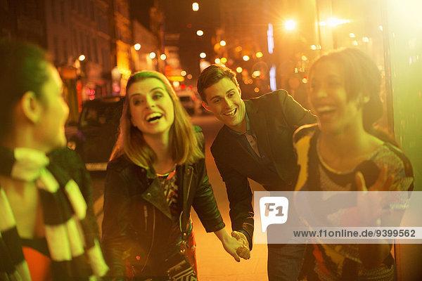 Freunde  die nachts zusammen die Straße entlanggehen.