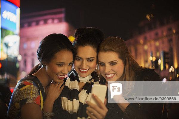 Frauen, die nachts auf der Straße miteinander reden.