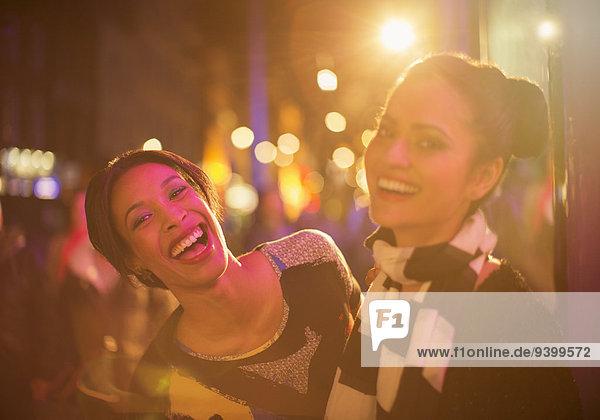 Freunde  die nachts auf der Straße lachen.