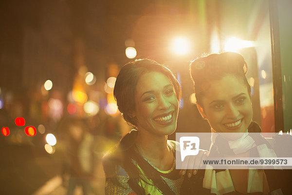 Frauen, die nachts auf der Straße lächeln.