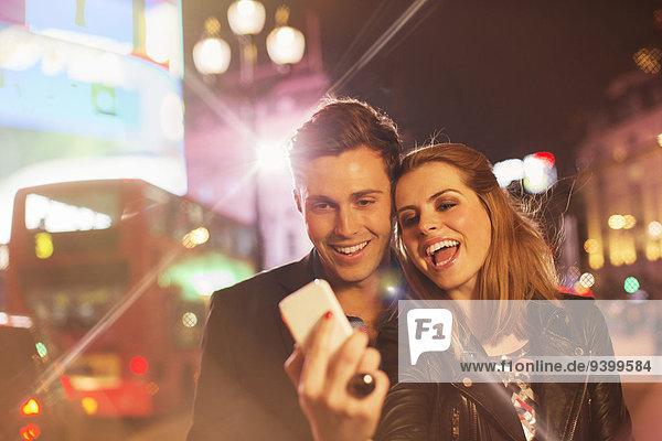 Ein Paar macht nachts gemeinsam ein Handyfoto auf der Stadtstraße.