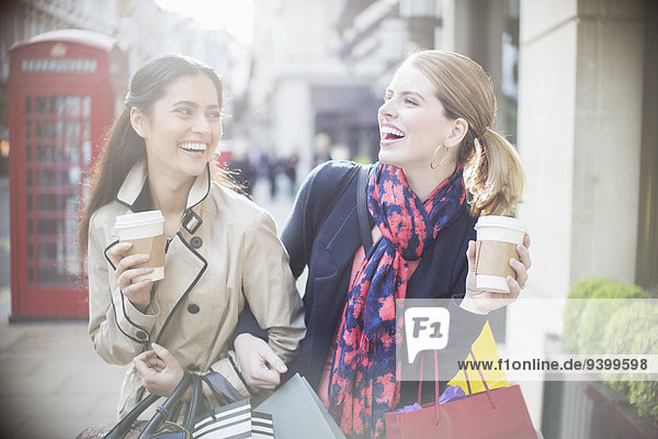 Women drinking coffee together on city street
