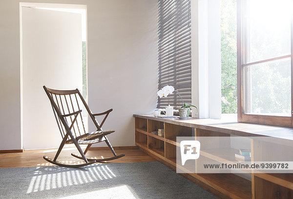 Schaukelstuhl und Teppich im modernen Schlafzimmer