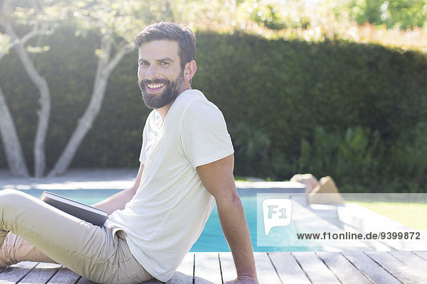 Smiling man relaxing on wooden deck by swimming pool