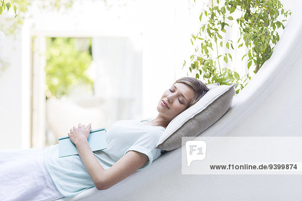 Frau entspannt sich auf Kissen im Freien