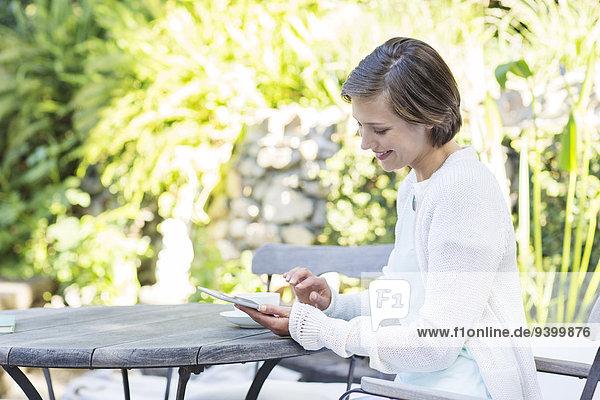 Frau mit digitalem Tablett am Tisch im Freien