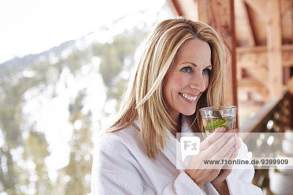 Frau beim Trinken auf dem Kabinenbalkon