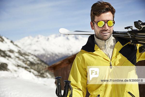Mann mit Skiern auf dem Berggipfel