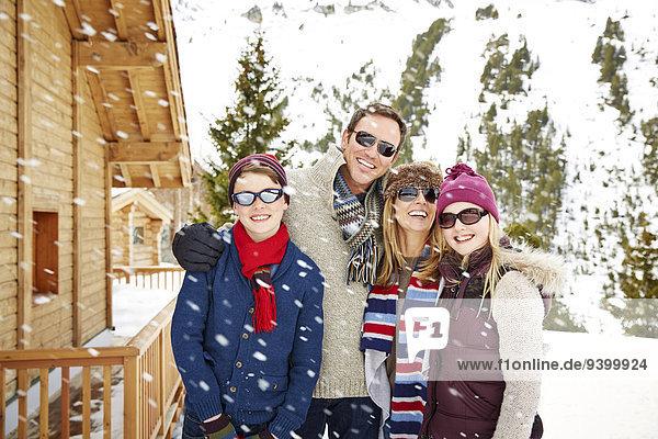 Familie lächelt gemeinsam im Schnee