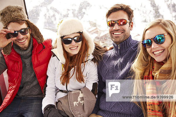Freunde lächeln gemeinsam auf dem Skilift
